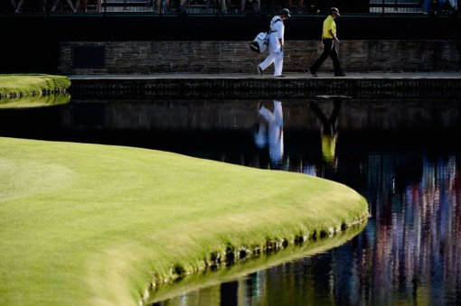 Bubba Watson and his caddie, Tom Scott, take a walk along the water on the 15th hole during Thursday's action. Photo: Harry How/Getty Images