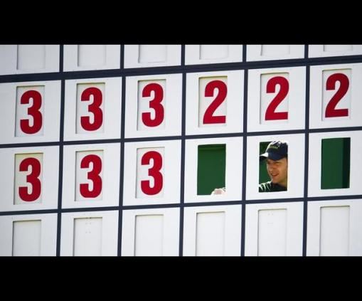 A course worked adjusts the score board during the second round at Augusta. Photo: Michael Madrid/USA Today Sports