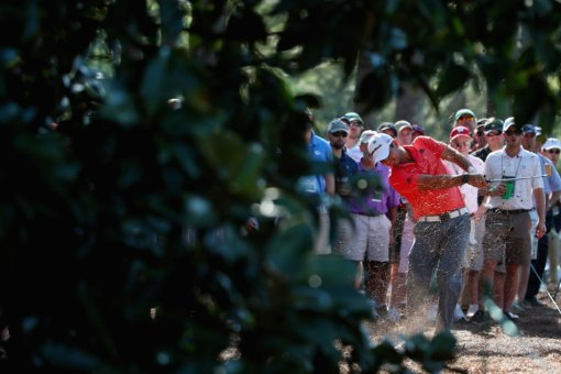 Jason Day is captured here taking a shot from the woods on the 14th hole Thursday.  Photo: Andrew Redington/Getty Images